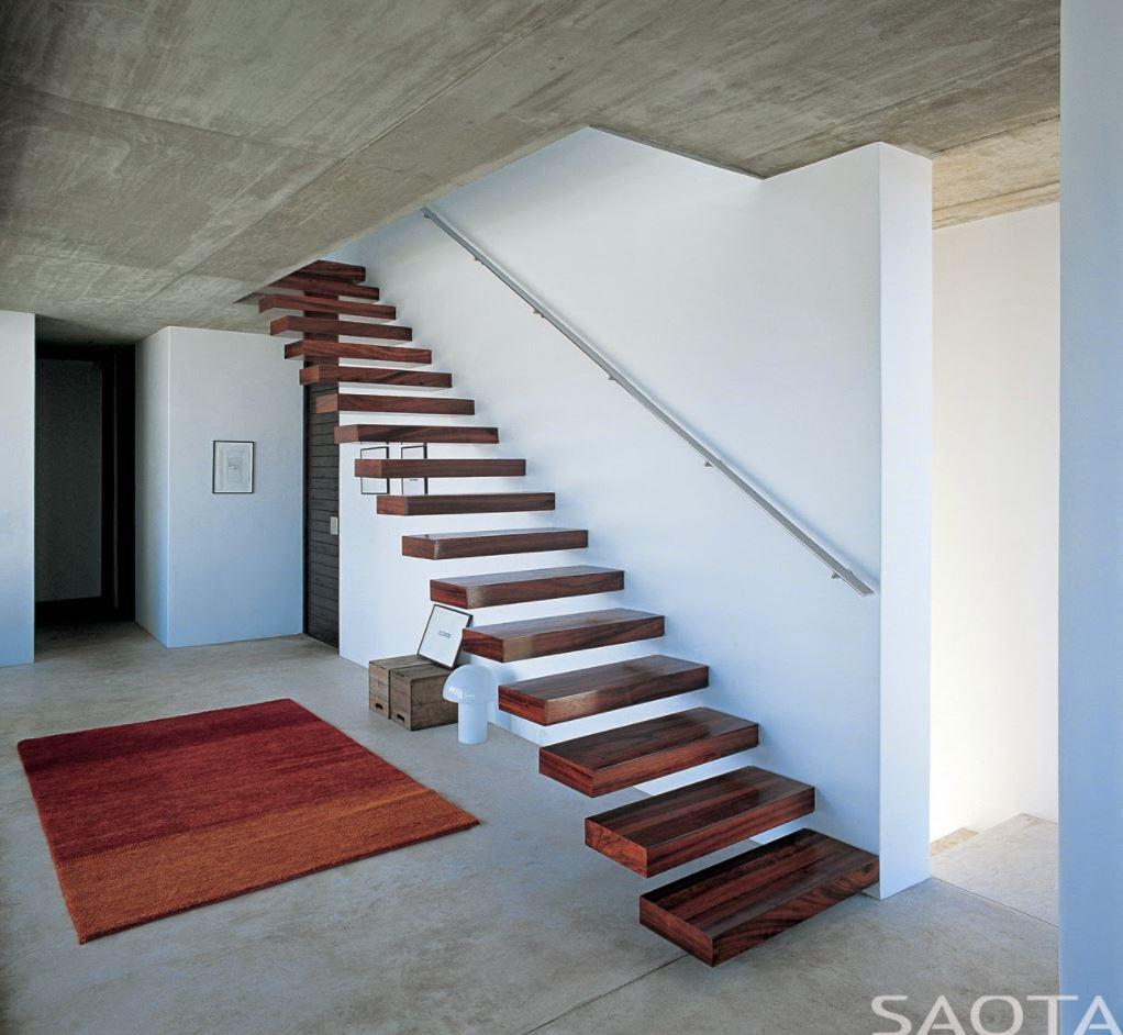 Casa de 2 pisos con ventanales y escalera flotante de madera for Escaleras para casas de 2 pisos