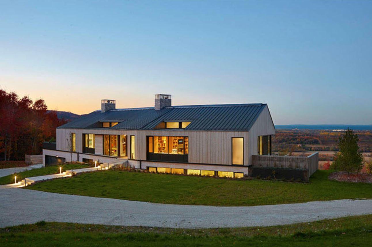 Casa en desnivel de dos plantas y techo de chapa for Casa moderna a dos aguas